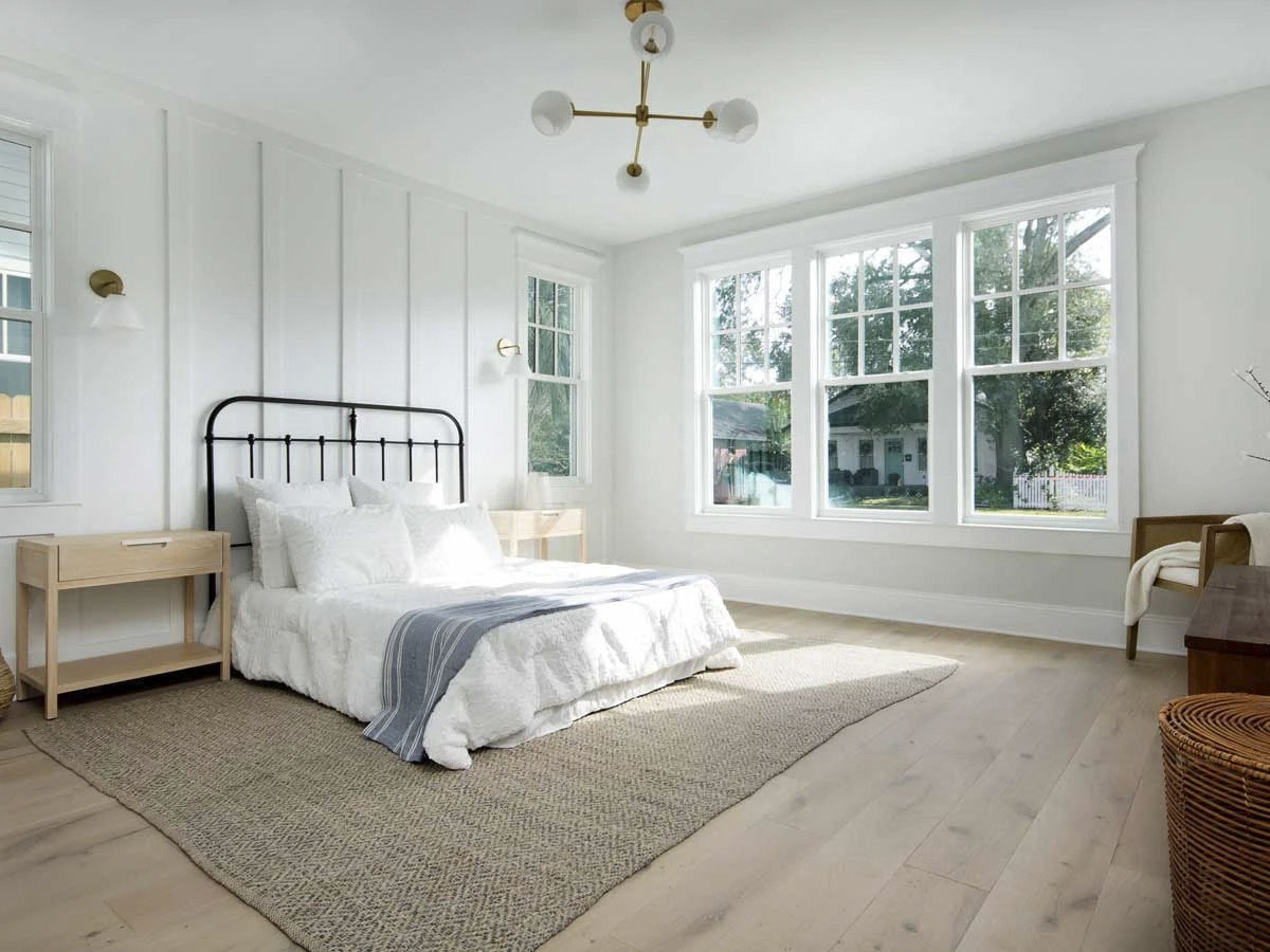 Primary bedroom with plenty of glass windows, a paneled accent wall, and a metal bed sitting over a jute area rug.