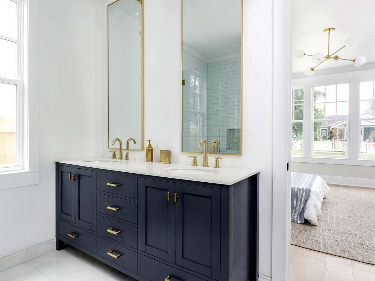 The primary bathroom features a dual sink vanity with black cabinets and brass accents.