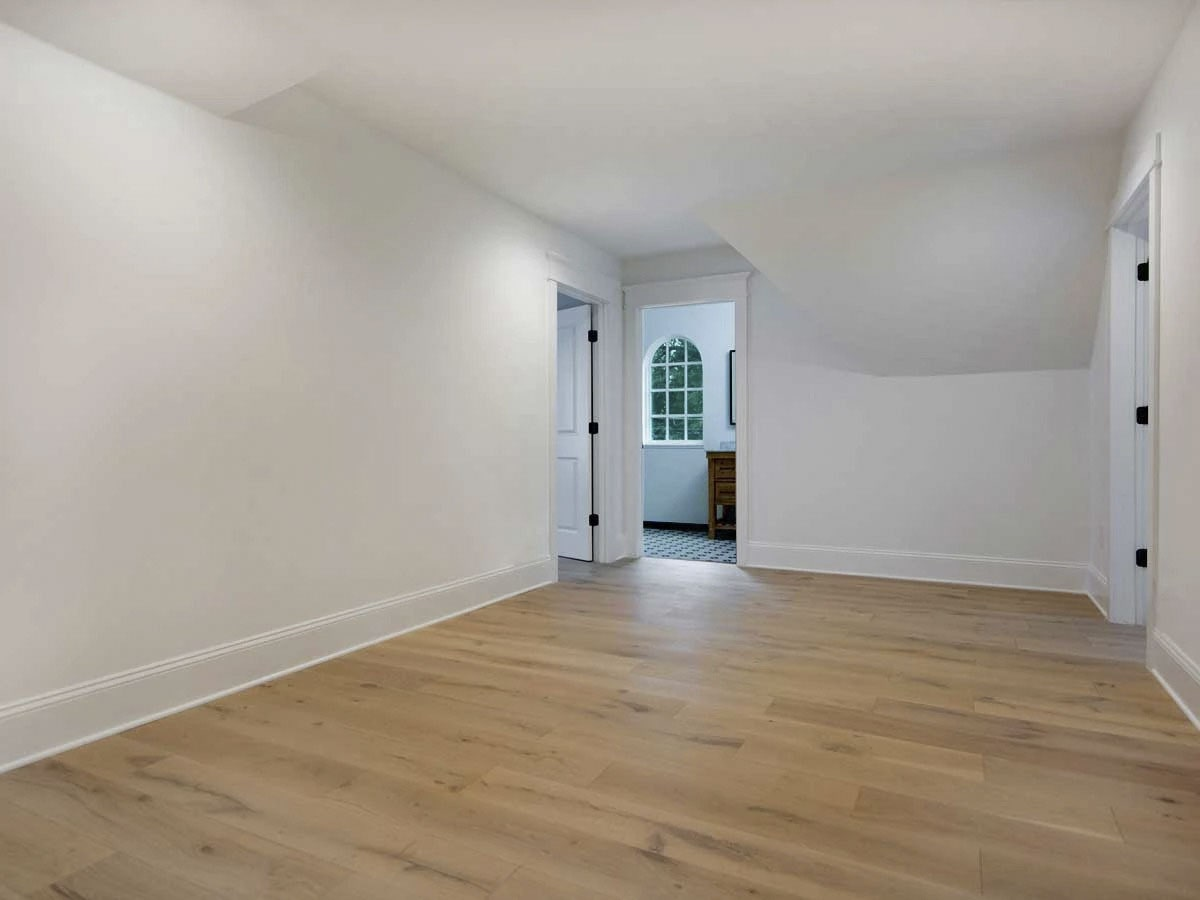 Another bedroom with wide plank flooring and stark white walls lined with base molding.