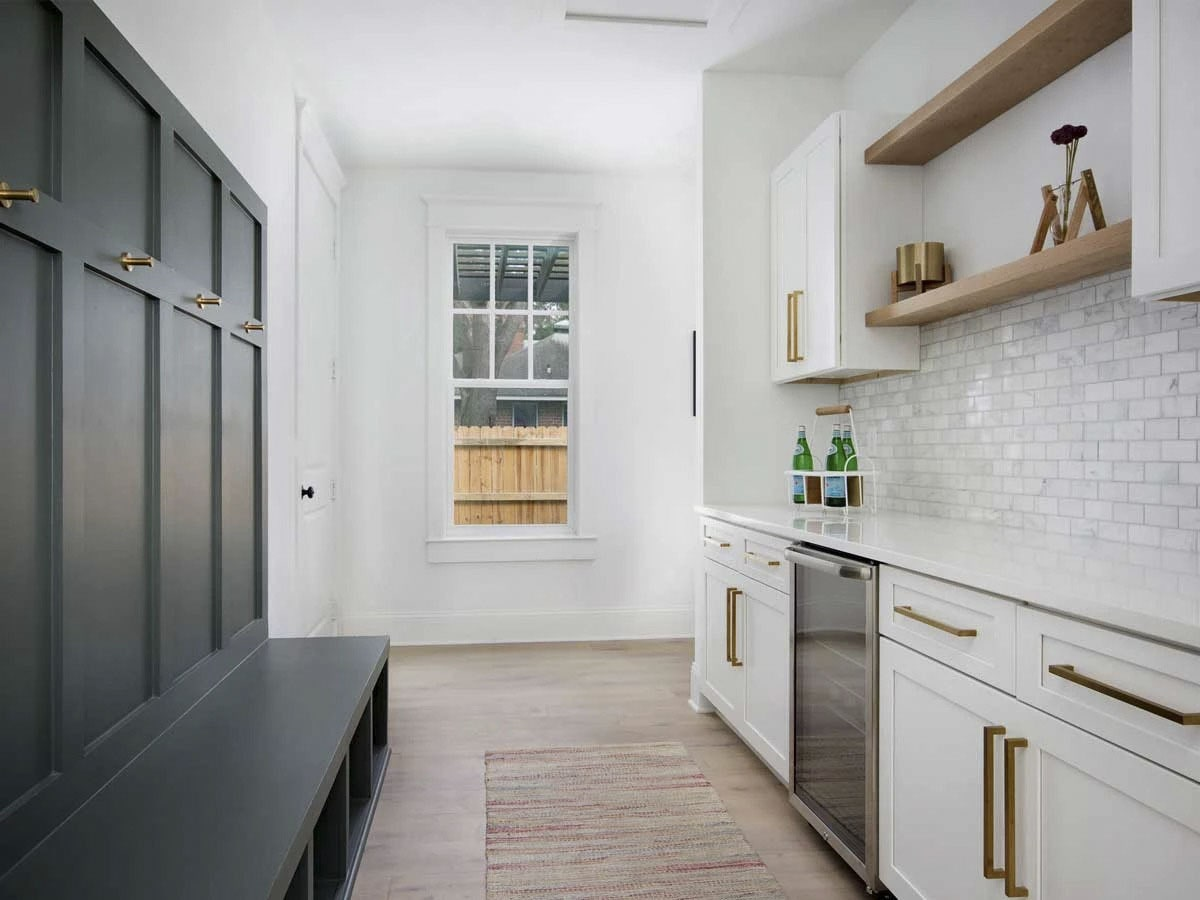 Mudroom with built-in bench, coat racks, and a quartz counter fitted with beverage fridge.
