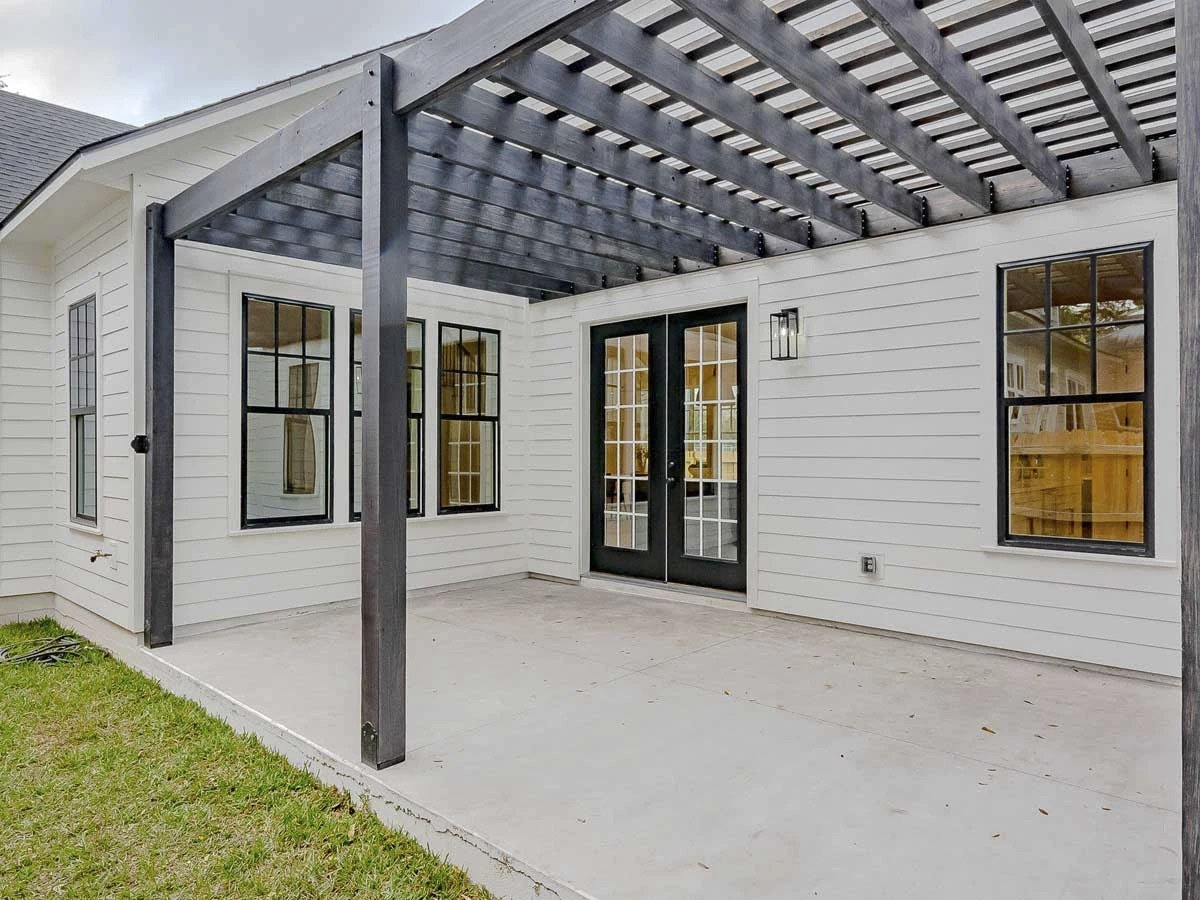 Covered patio with trellis roof, dark wood posts, and concrete flooring.