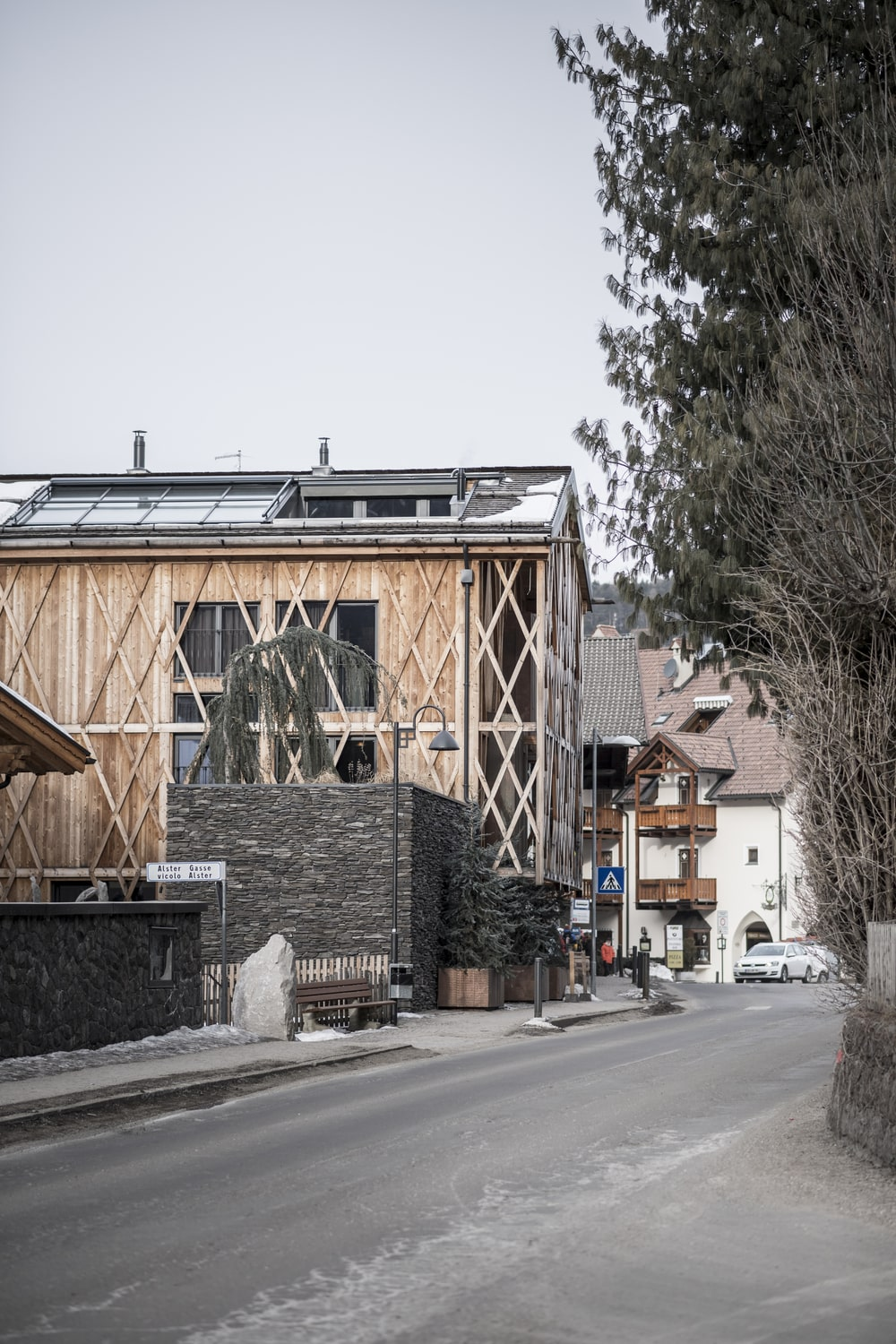 This is a street view of the house that has unique intricate patterns on its wooden exteriors.