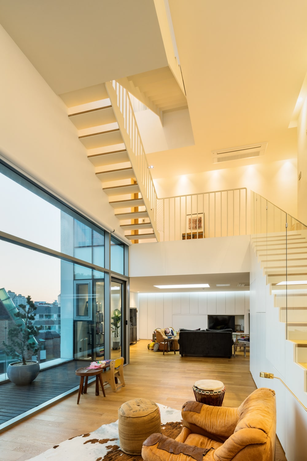 This is an interior view of the building with a comfortable cushioned armchair by the large glass wall that leads to the balcony.