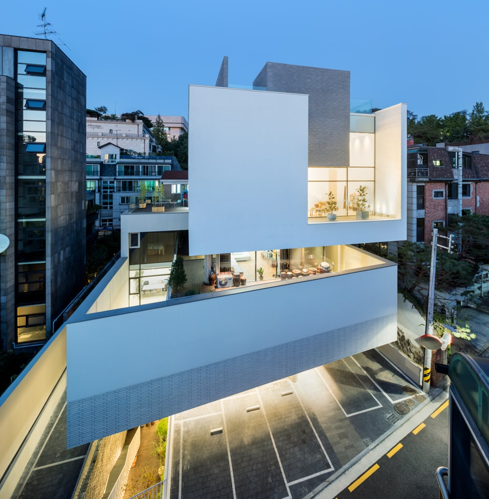 This is an aerial view of the building with a focus on the warm glow of the glass walls.