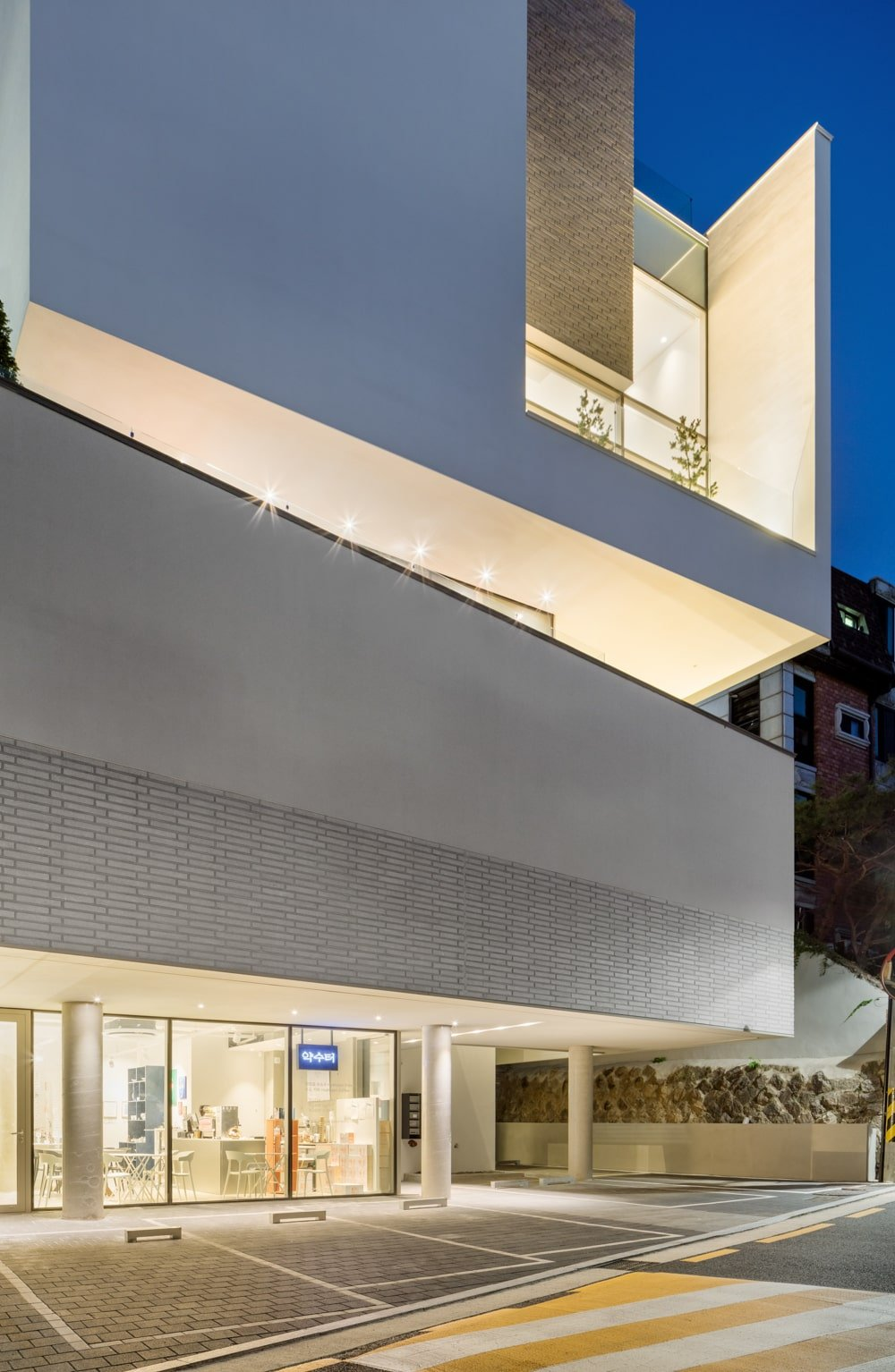 This is a close look at the side of the building showcasing the warm glow of the glass walls and balconies supported by the concrete structures.