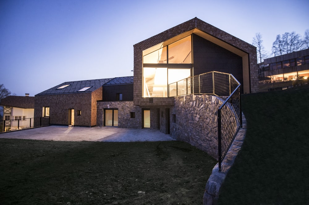 This is a nighttime view of the house that showcases the warm glow of the glass walls that come from the interior lights.