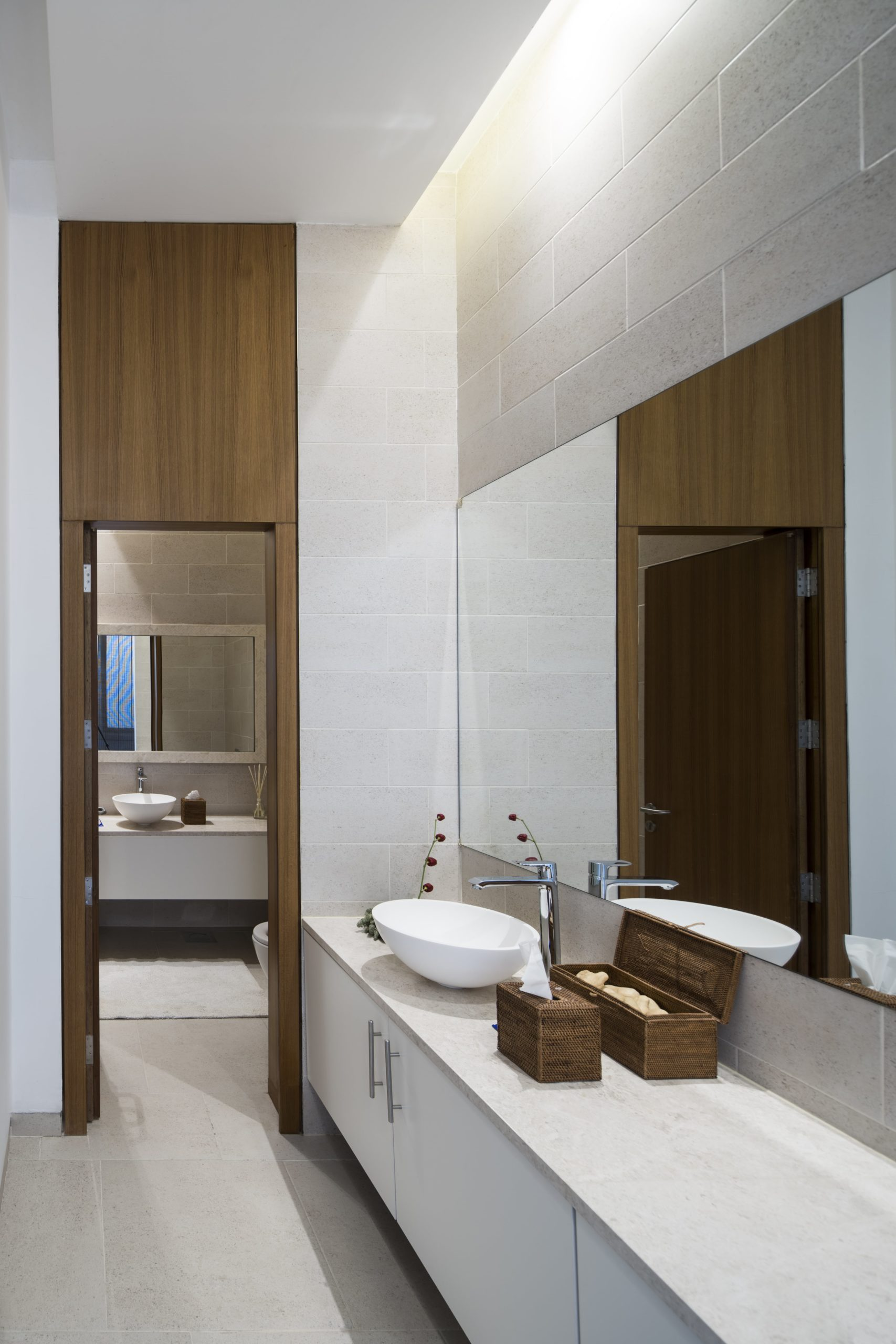 The bathroom has a large vanity topped with a modern wall-mounted frameless mirror.