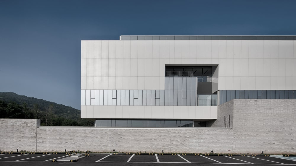 This is a side of the building with parking spots in front of the modern set of windows on the upper floor.