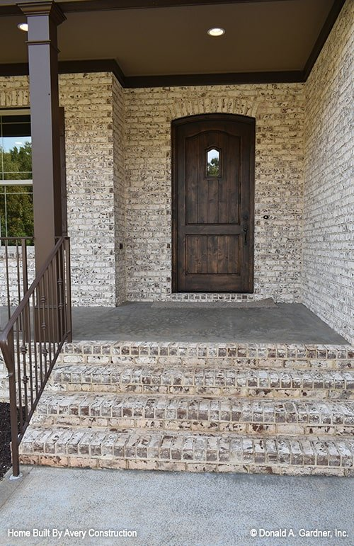 The front porch includes a stone stoop and a wooden entry door.