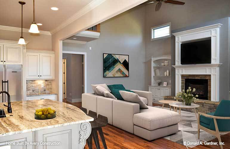 The living room offers a modern gray sectional, cushioned armchair, modular coffee table, and a fireplace with a TV on top.