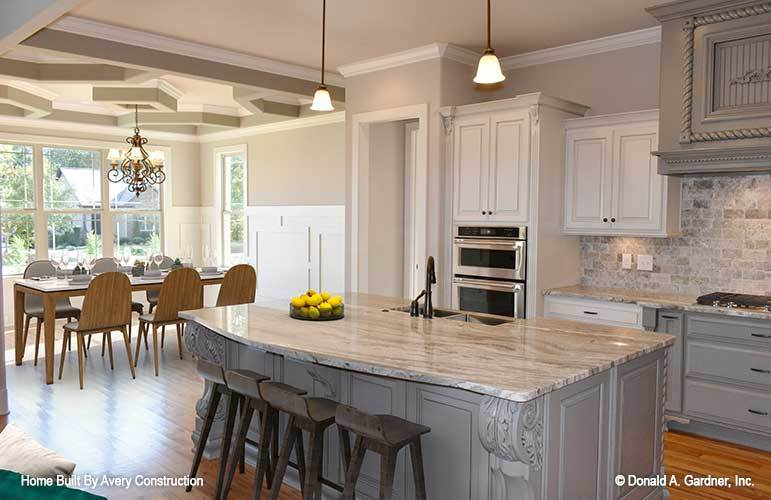 The kitchen is equipped with white and gray cabinets, a brick backsplash, marble countertops, and a large breakfast island.