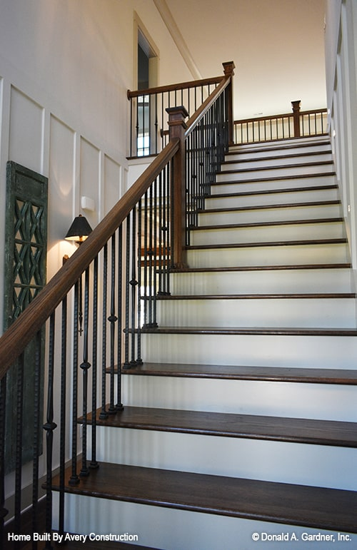 Staircase with wooden wrought iron spindles and dark wood treads matching with the handrails and posts.