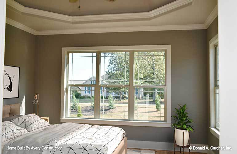 Primary bedroom with an elegant tray ceiling and a trio of windows that invite natural light in.