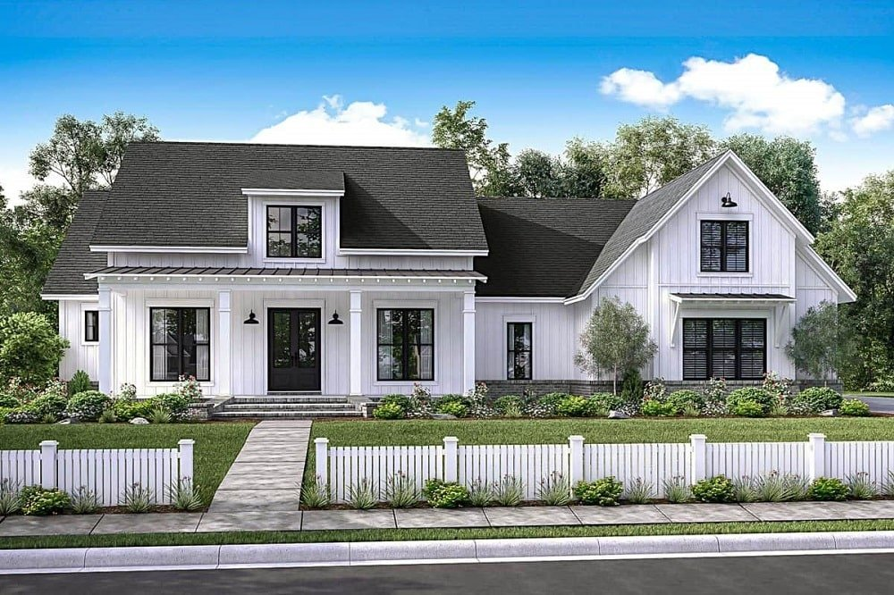 The bright white walls of the farmhouse-style home is contrasted by the dark gray roof above with a dormer window and complemented by the landscaping of shrubs, grass and white picket fences.