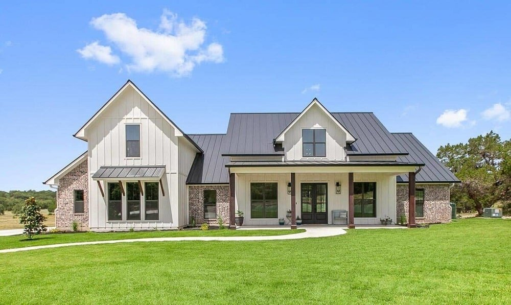 This is a bright and welcoming modern farmhouse-style home with dark gray roof and bright beige exterior walls complemented by the glass windows and doors.