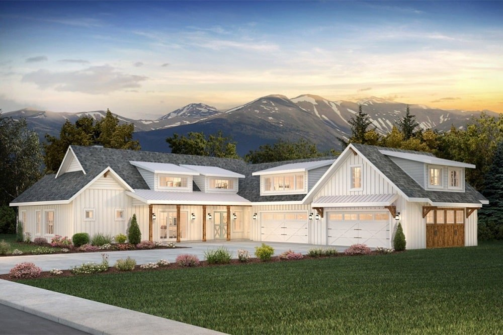 This is a large two-story modern farmhouse-style home with beige exterior walls that glow warmly from interior and exterior lights that also brighten the driveway.