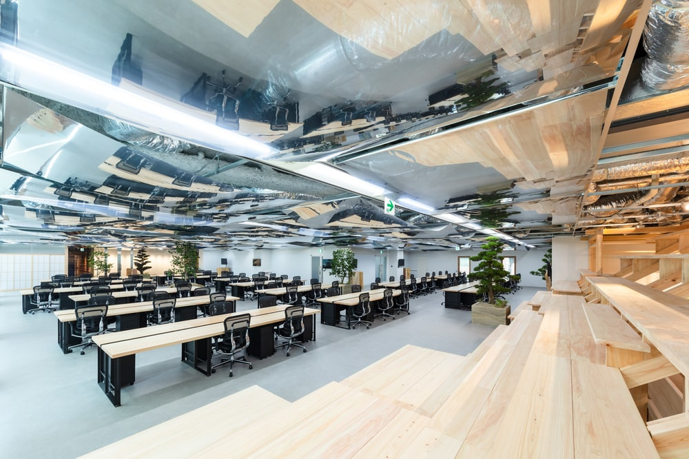 This isa look at the large open office space with multiple wooden tables and office chairs topped with shiny silvery materials on the ceiling.
