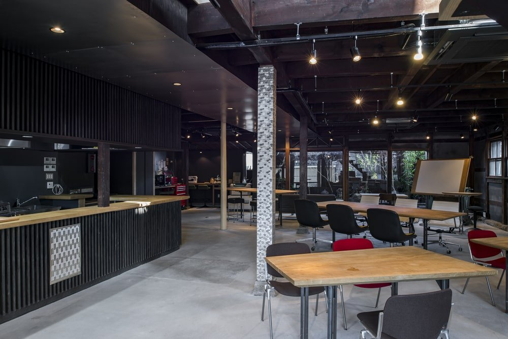 This view of the large room showcases the modern lighting and dark tones of the structures.
