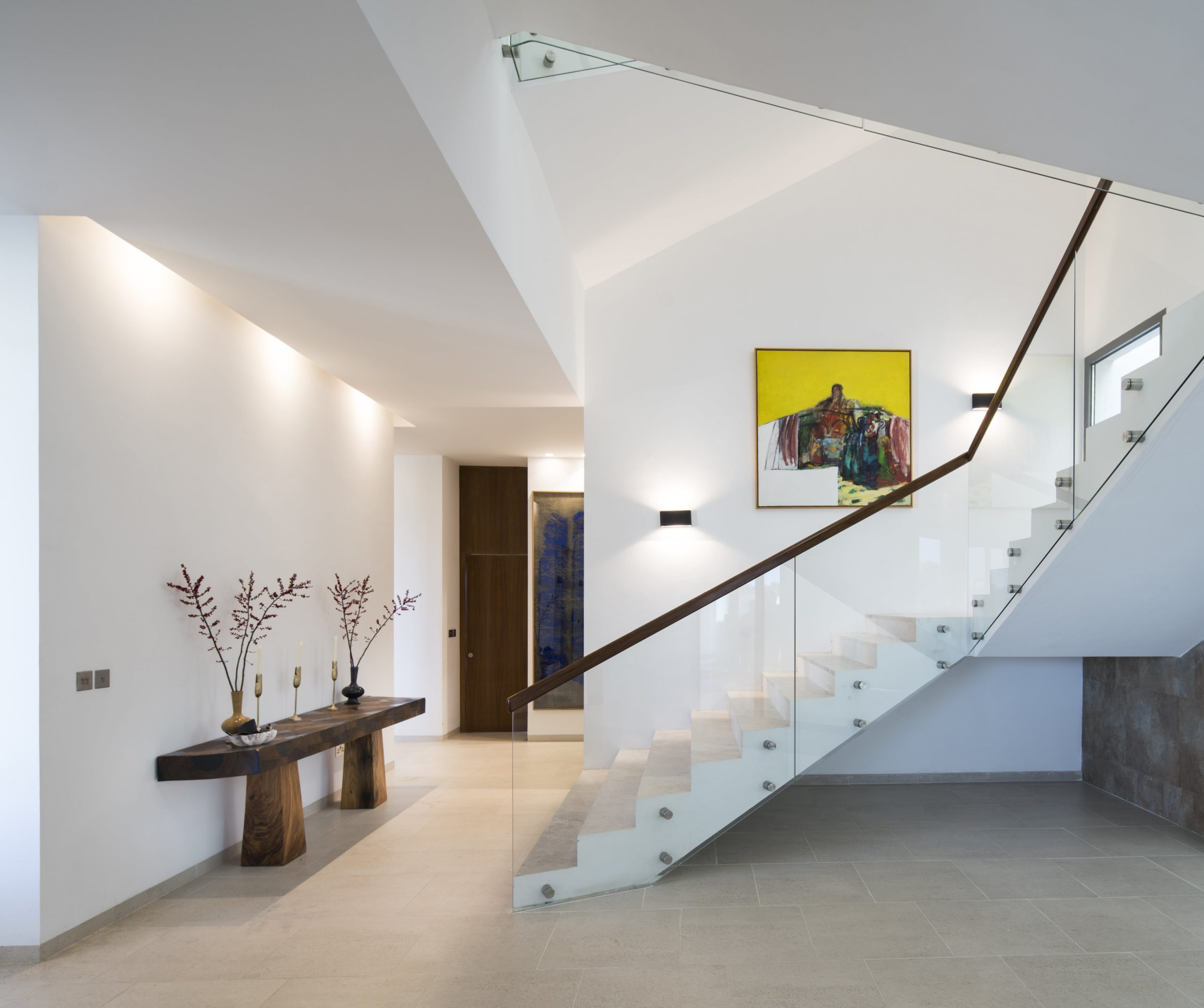 Upon entry of the house, you are welcomed by this simple foyer that has a wooden console table topped with decors and has a white staircase.