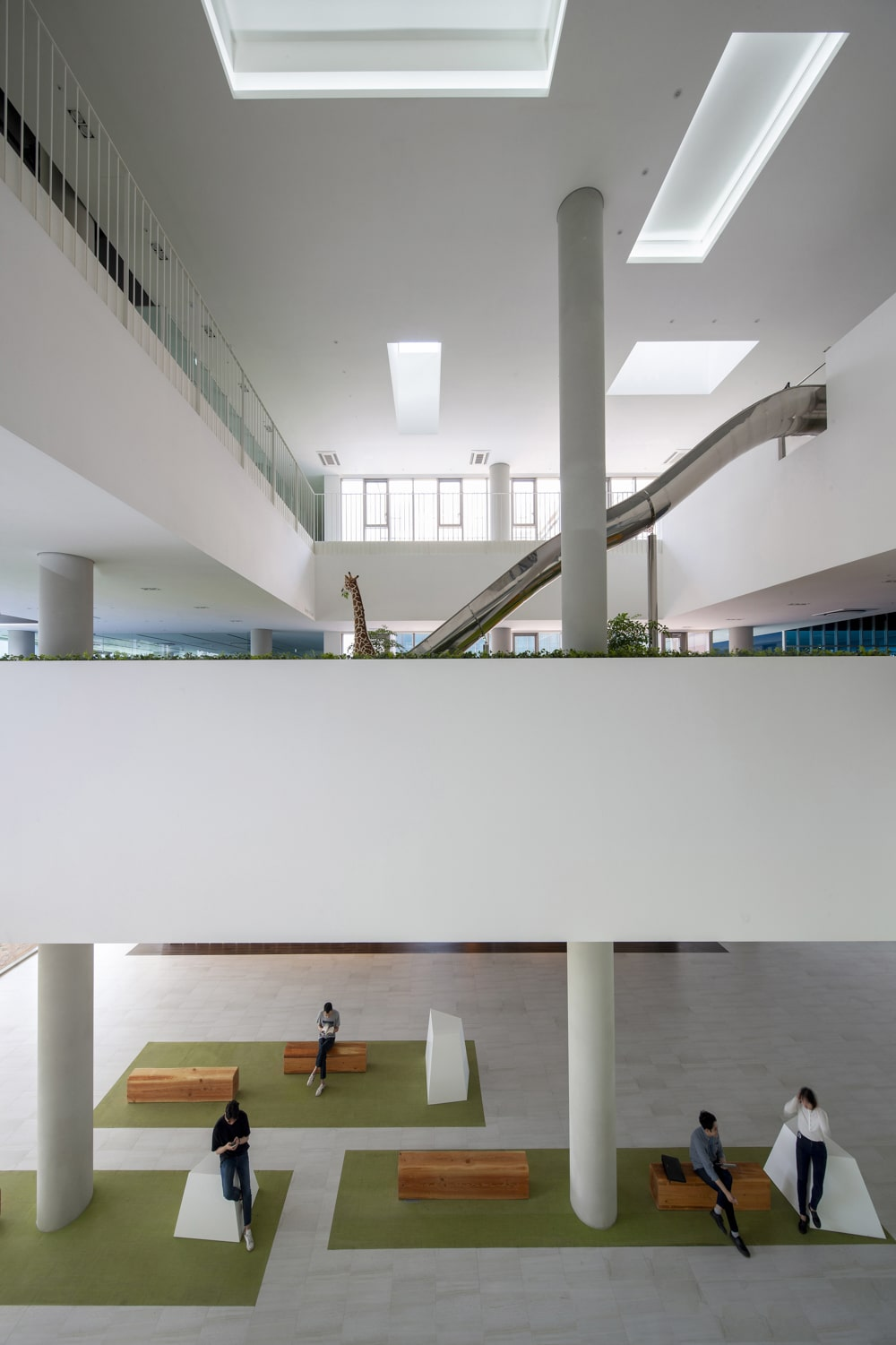 This is a look at the large interior of the building lobby with a tall ceiling that has skylights.