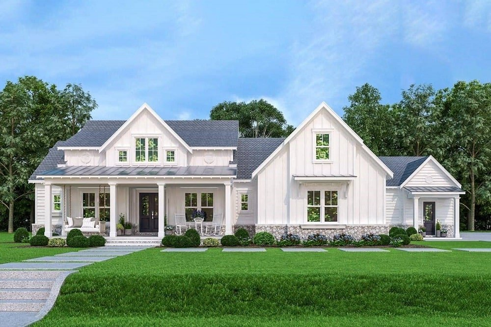 The bright beige exterior walls of this farmhouse-style home pairs well with the gray roof and lush green landscaping with shrubs on the side flanking the main entrance.