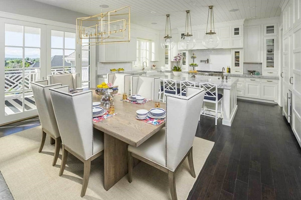 Shared dining and kitchen with dark hardwood flooring and white shiplap ceiling mounted with brass and glass globe pendants. The dining has a wooden table surrounded by cushioned chairs.