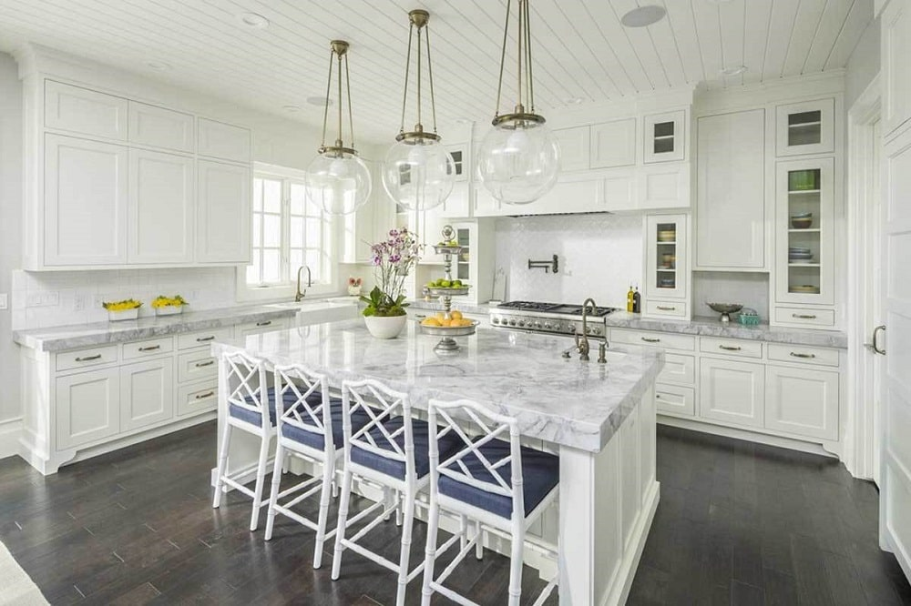 This is a bright kitchen with white shaker cabinets and white marble countertops topped with glass pendant lights contrasted by the dark hardwood flooring.