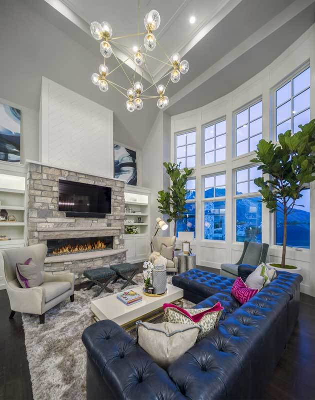 The decorative and artistic chandelier hanging from the tall ceiling complements the tufted sectional black sofa across from the wall-mounted TV above the modern fireplace.