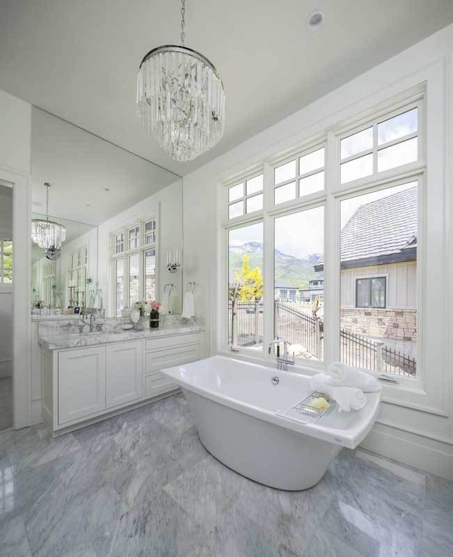A glass cascading chandelier illuminates this bathroom with a marble top vanity and a freestanding tub by the white-framed windows.