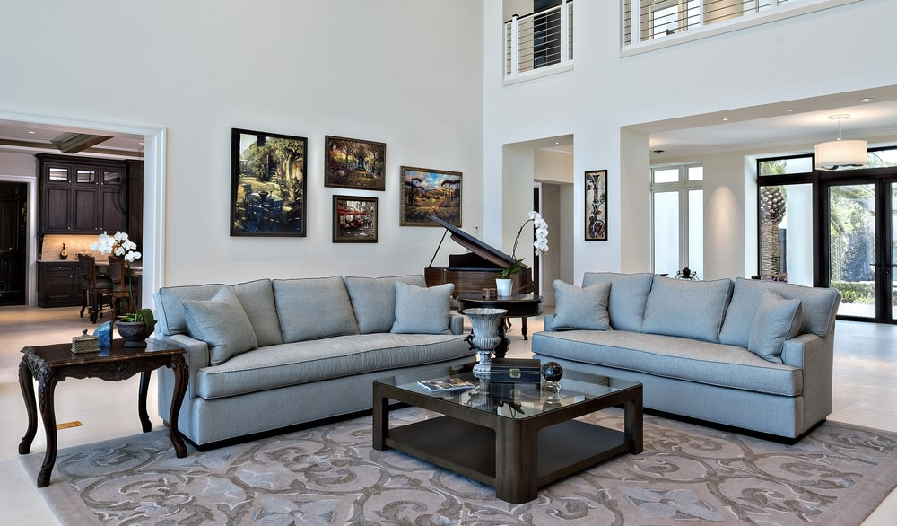 This is a close look at the gray sofa set paired with a large dark wooden coffee table on a patterned area rug.