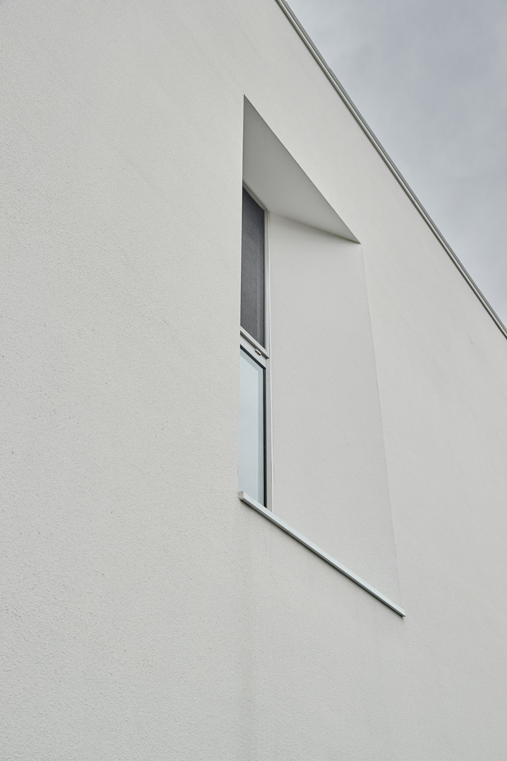 This is a closer look at the window of the upper floor that has a unique embedded design and angled position.