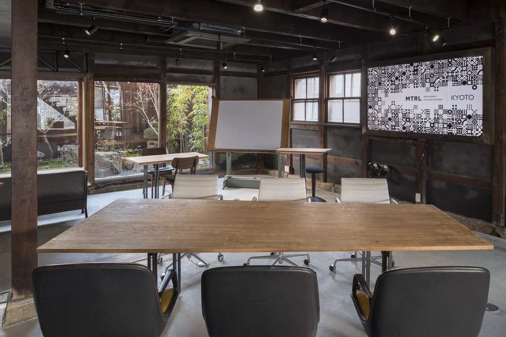 This is a close look at the other large rectangular wooden work table surrounded by gray upholstered chairs.