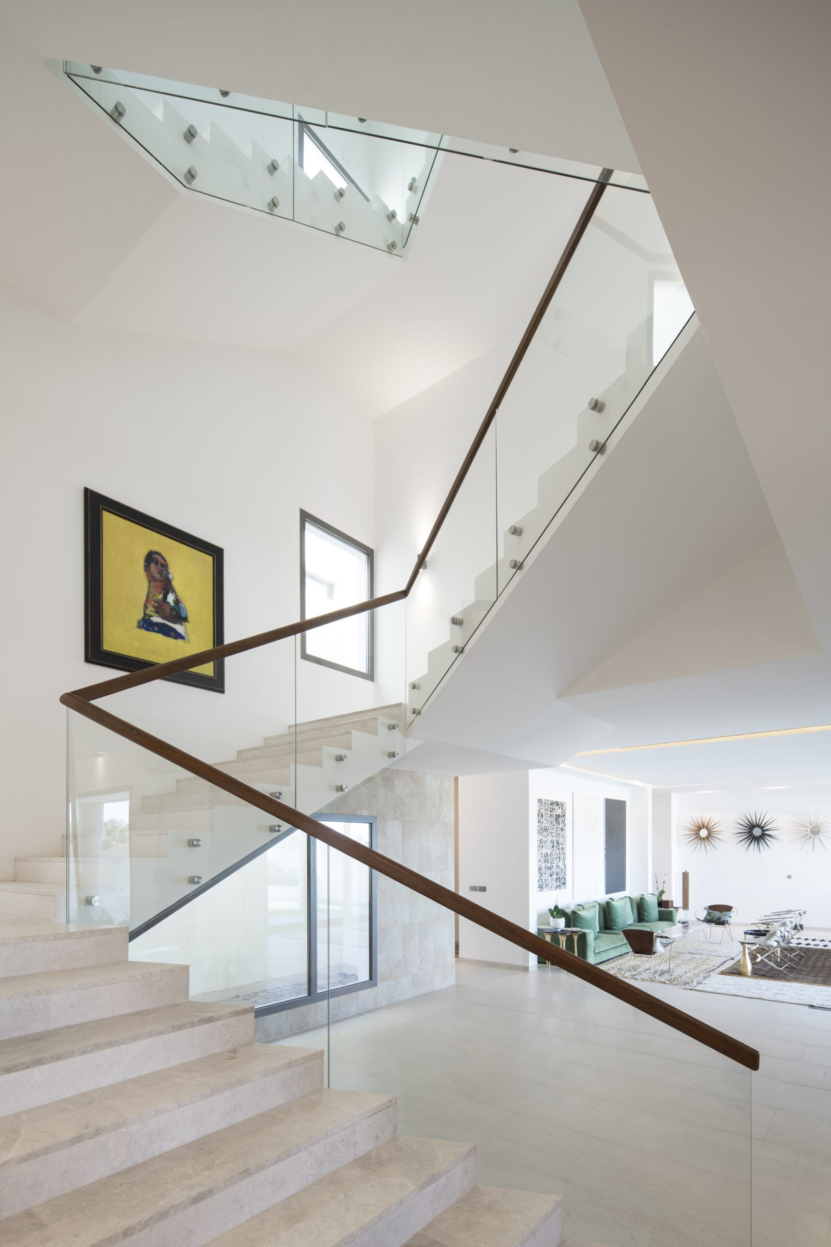 This is a look at the staircase that has a modern white design and a glass railings.