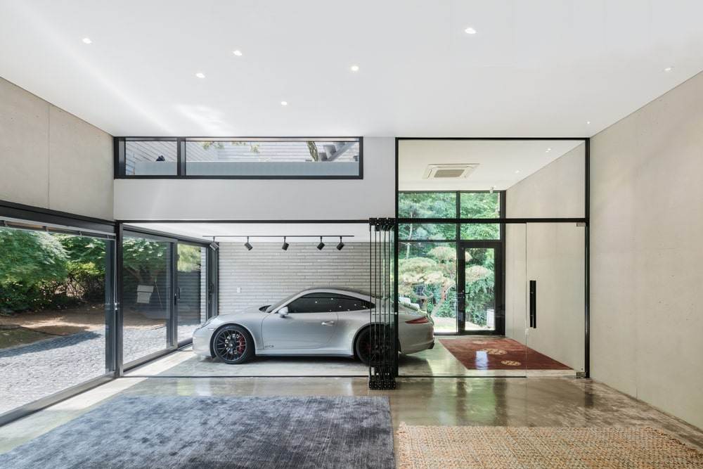 This is a close look at the garage that has glass walls and glass doors for a sleek design paired with bright white walls and ceiling.