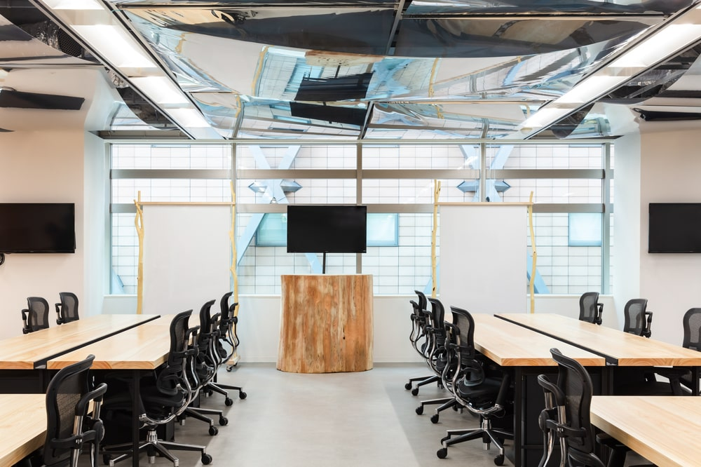 This is a close look at an open plan setup office area with large wooden tables paired with office chairs to accomodate large quantities of employees.