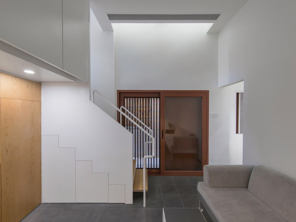 The side of the sofa is the small foyer with a large brown main door with a glass panel on the side and a staircase.