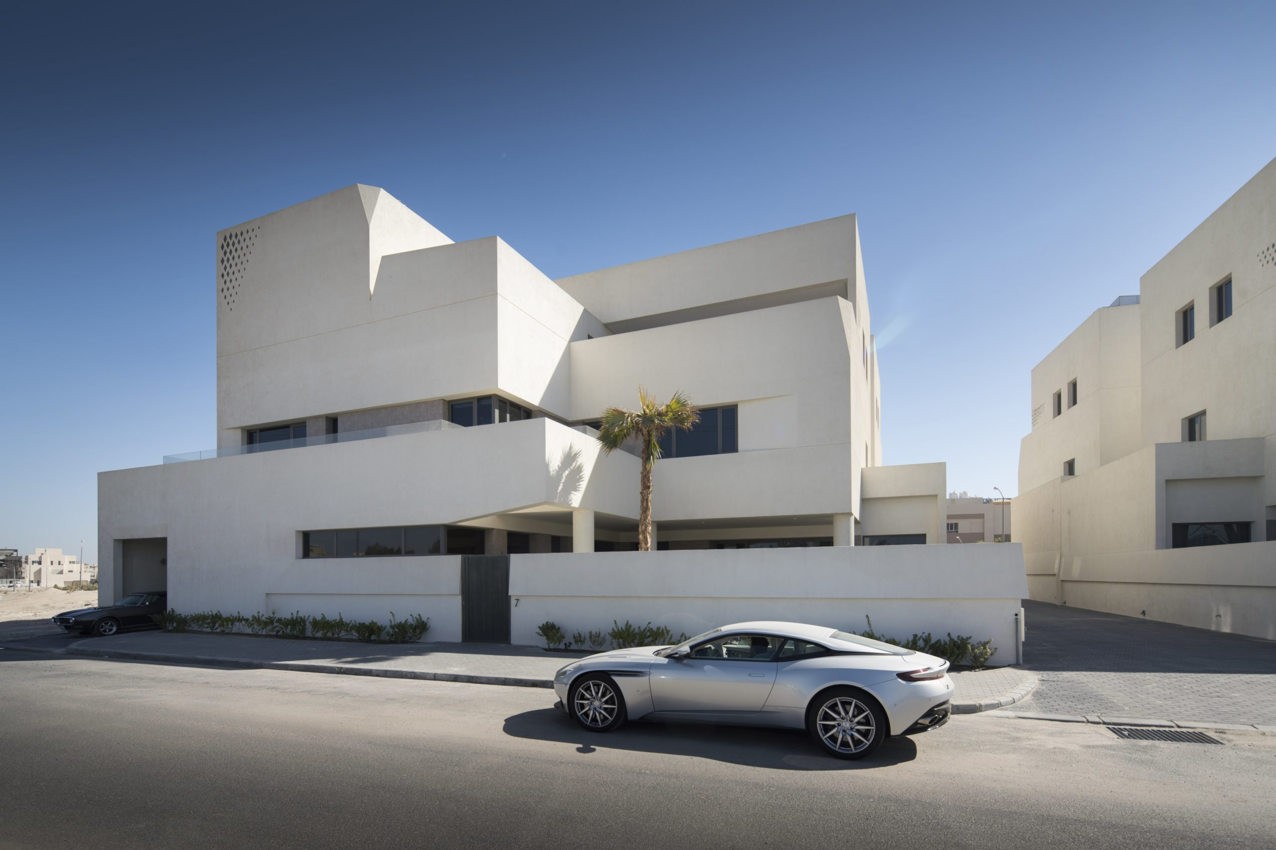 This is a view of the front of the house that has a modern design and bright exterior walls.