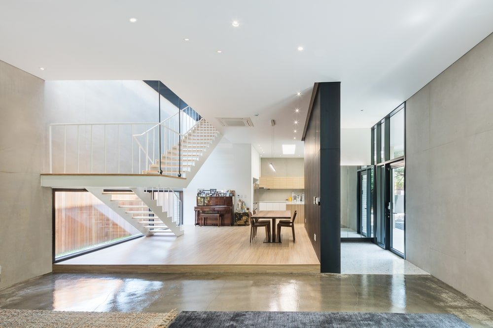 You can see here the simple foyer of the house with a glass door welcomed by a large dark wall that separates the dining area with the foyer.