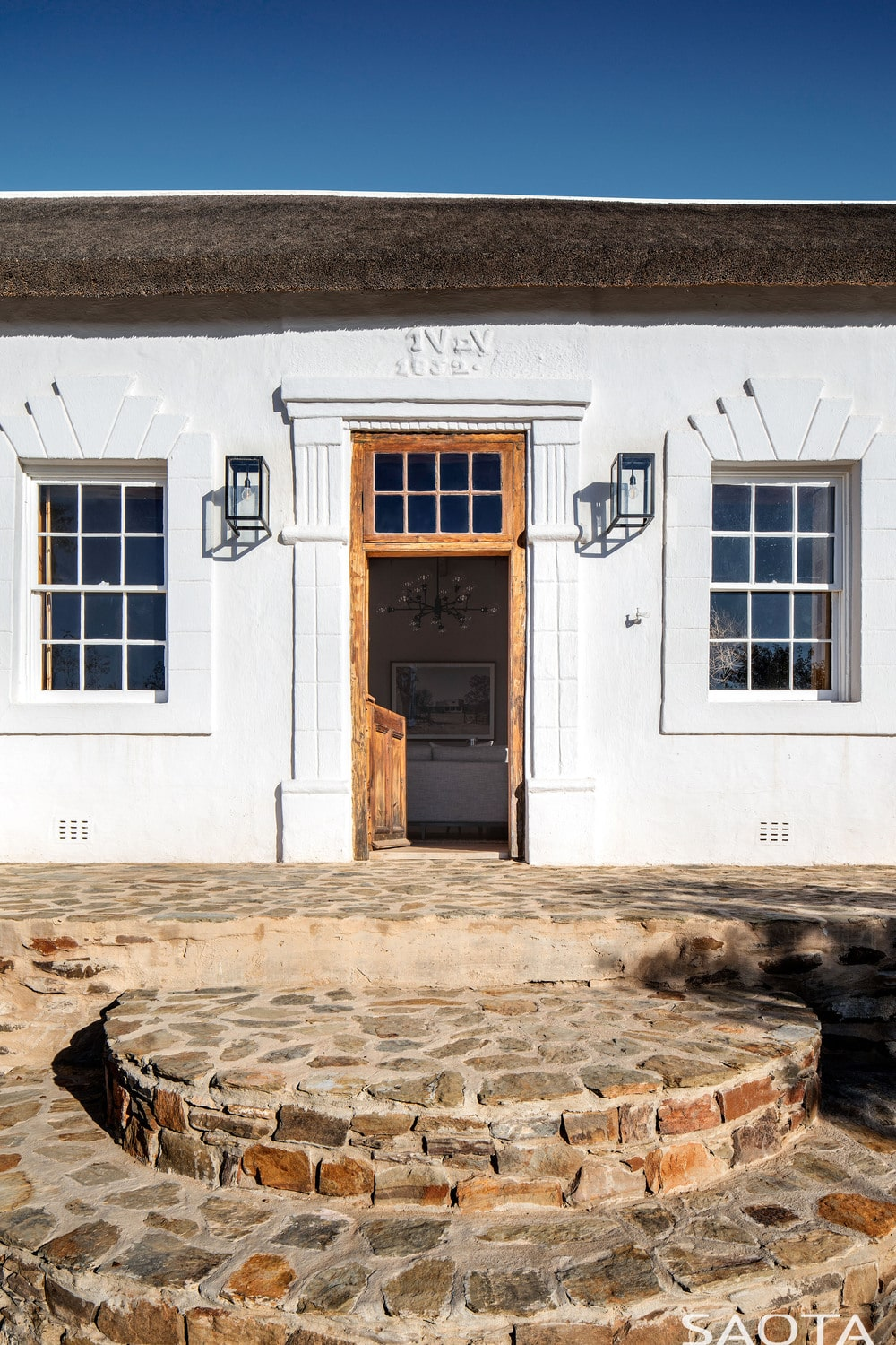 This is the main entrance of one of the houses with a couple of rustic stone steps and wooden main door flanked by wall lamps.