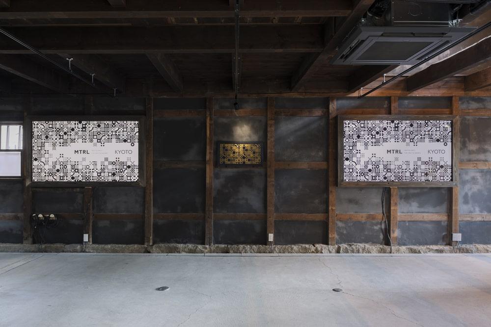 This is a close look at the dark-tone wall with exposed wooden beams showcasing the wall-mounted artworks.