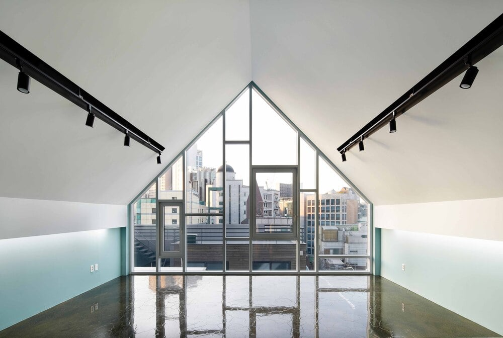 This is an interior view of the house showcasing the large glass wall on the far side that shows the city skyline.