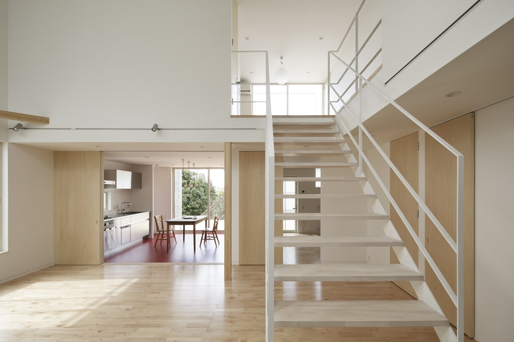 This is the interior view of the house that has a white staircase with a view of the kitchen on the far side.