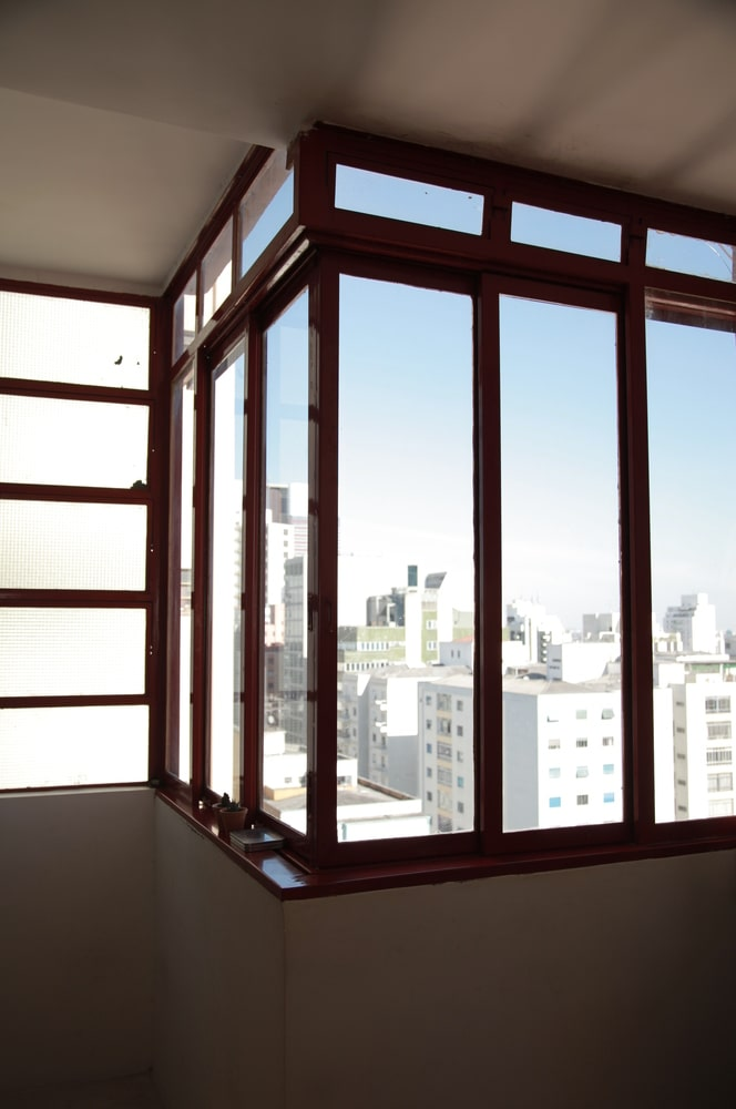 These corner windows have wooden frames that complement the surrounding beige walls and ceiling.
