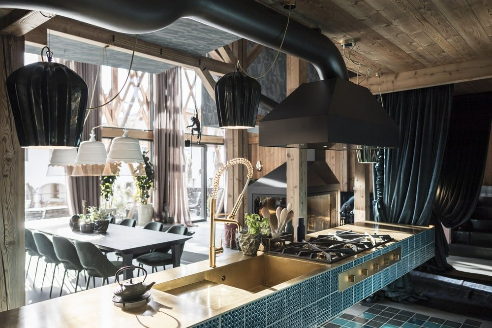 This is a close look at the cooking area with sea green tiles that make the black elements of the stove and vent hood stand out.
