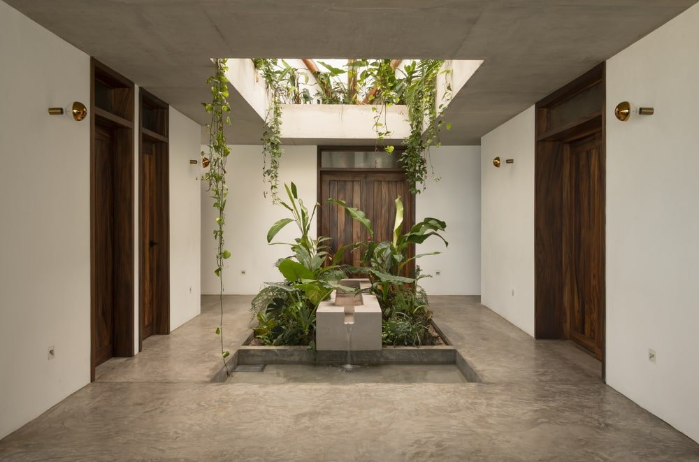 This is a look at the main entrance of the house with a miniature garden in the middle that also has a water feature to it.