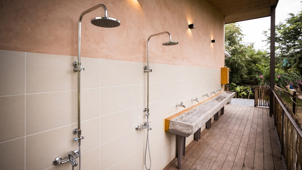 This is the outdoor public bathroom with shower areas and sinks on the wall.