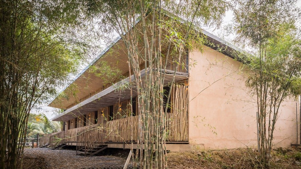 This is an angled view of the dormitory with concrete walls on the side and bamboo accents on the front side.