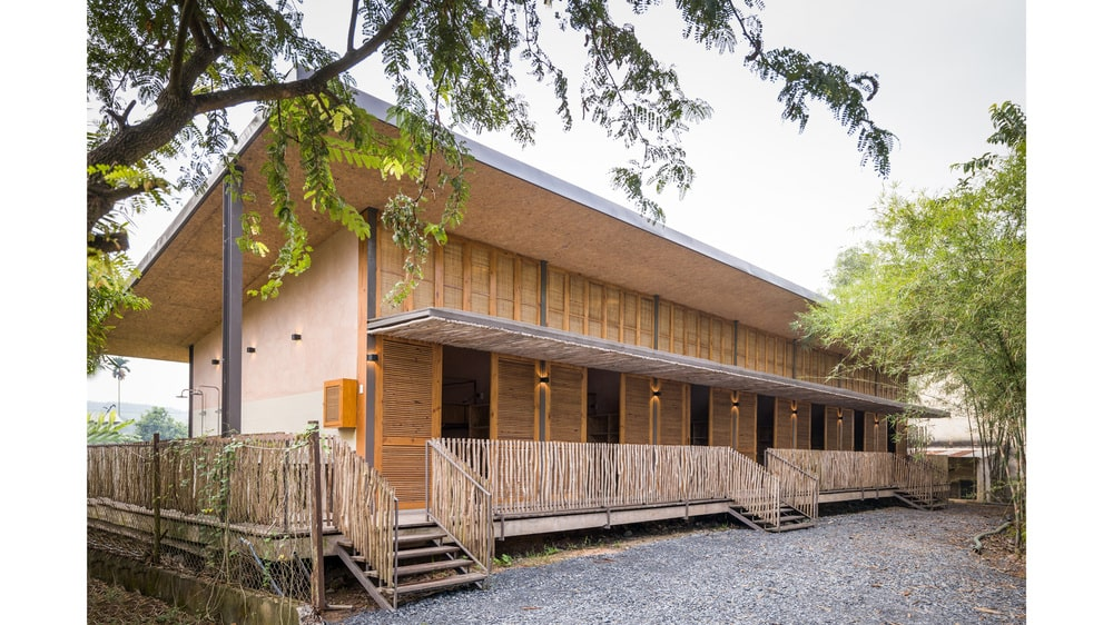 The dormitory has multiple wooden steps that access the courtyard from its porch.
