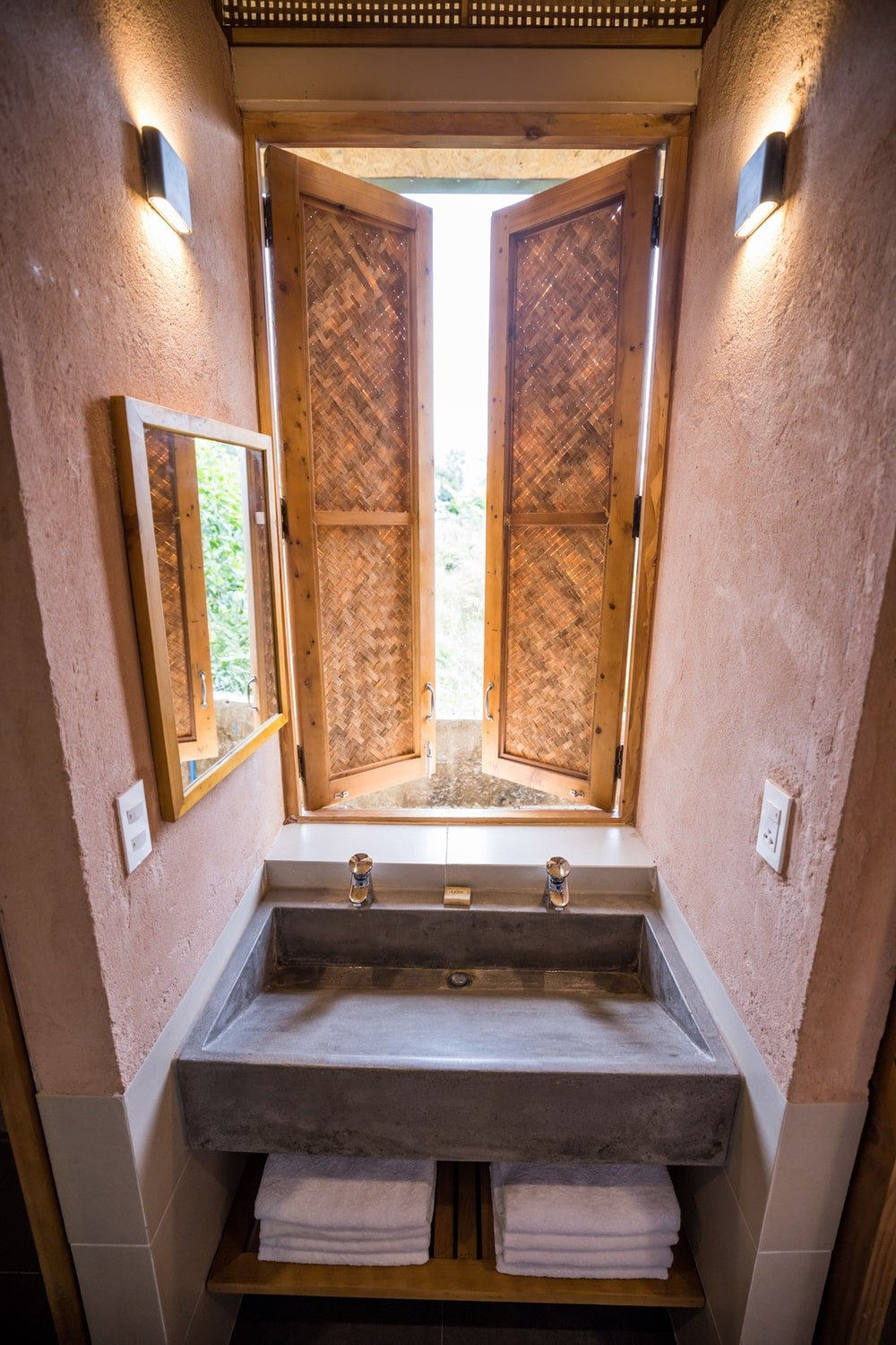The private bathroom has a stone sink paired with a set of woven wicker windows.