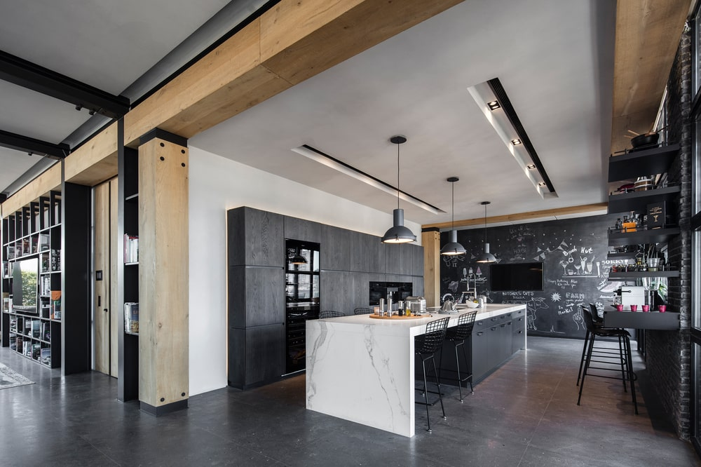 The kitchen has a white marble waterfall counter that stands out against the dark floor, dark cabinetry and dark dome pendant lights hanging from the ceiling.